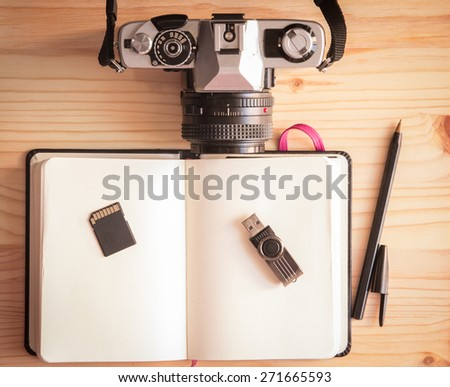 Retro vintage old photo camera with notebook, pen, pendrive, sd card and mouse on a wooden table - stock photo