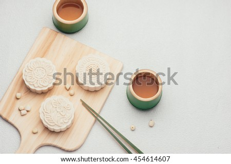 Retro vintage style Chinese mid autumn festival foods. Traditional mooncakes on table setting - stock photo