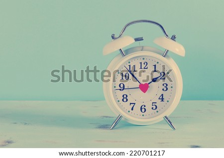 Retro vintage style classic white alarm clock on vintage blue background for daylight saving or time concept. - stock photo