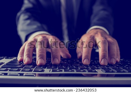 Retro vintage style image of a businessman typing on computer keyboard.  - stock photo