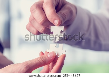 Retro vintage style image of a businesspeople fitting together matching interlocking puzzle pieces conceptual of teamwork and problem solving. - stock photo