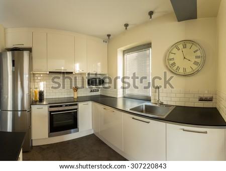 Retro wall clock in designed kitchen interior - stock photo