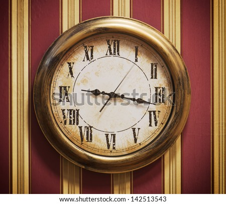Retro wall clock with striped wallpaper. - stock photo