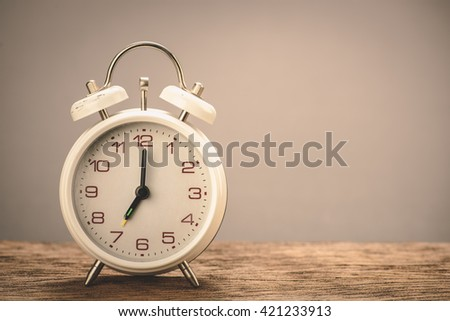 Retro white alarm clock with gray background - stock photo