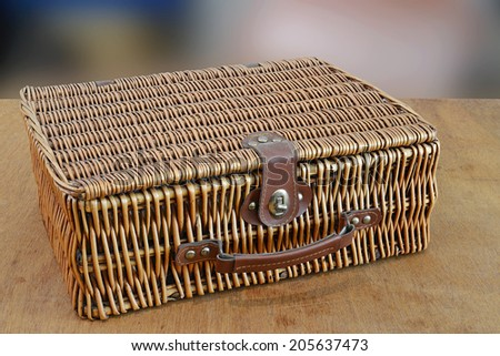 Retro wicker bag on a wooden table - stock photo
