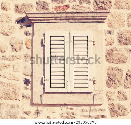 retro window with wooden shutters and stone walls - stock photo