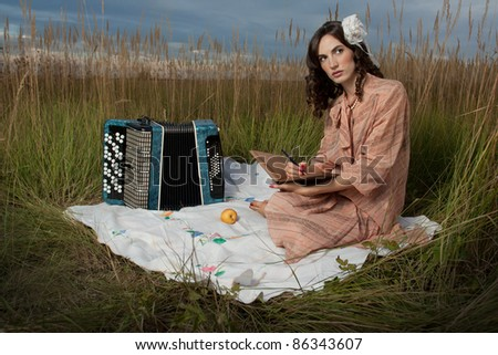 Retro woman seating with an accordion, book and pen, in a field of tall grass. - stock photo
