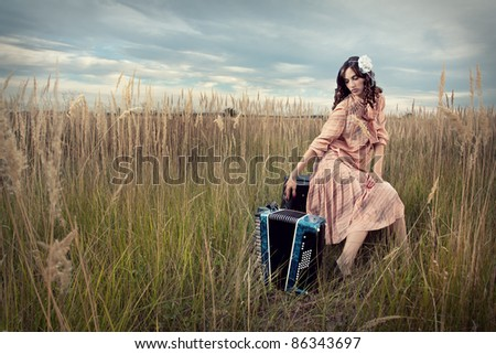 Retro woman sitting with an accordion, in a field of tall grass. - stock photo