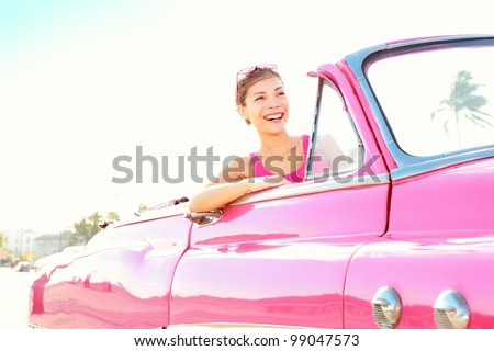 Retro woman smiling happy in old pink vintage car driving on road trip on beautiful summer day. Pretty multiracial Asian / Caucasian female model - stock photo