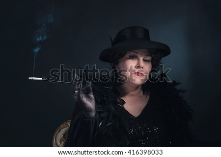 Retro woman wearing hat and smoking cigarette. 1930s classic portrait. - stock photo