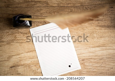 Retro workplace  with goose quill and ink pot on wooden table - stock photo