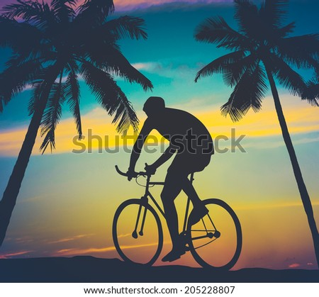 Retro Worn Style Photo Of A Man Cycling By Tropical Palm Trees - stock photo