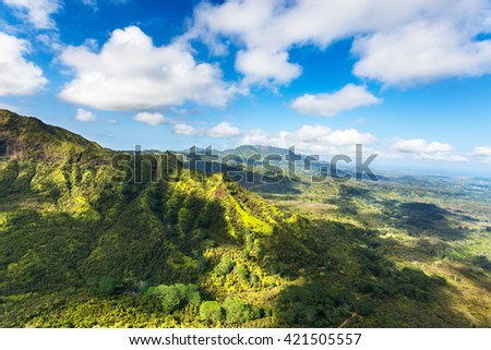 Returning to Lihue airport from Hanalei Valley with cloud shadows dotting the vibrant green landscape - stock photo