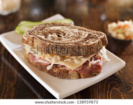 reuben sandwich with kosher dill pickle and coleslaw - stock photo