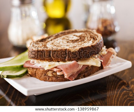 Reuben sandwich with kosher dill pickle and coleslaw on plate - stock photo
