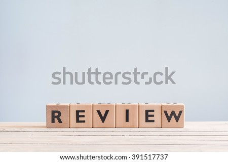 Review headline sign made of wood on a table - stock photo