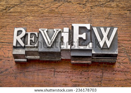 review word in mixed vintage metal type printing blocks over grunge wood - stock photo