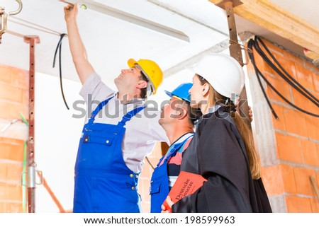 Reviewer or expert or lawyer and builder or worker with helmets controlling a construction or building site to report defect or fault or deficiency in a protocol - stock photo