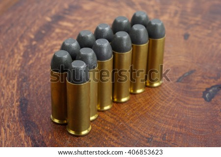 Revolver cartridges .45 Cal Wild West period on wooden background - stock photo