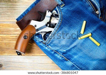 revolver in the pocket of old blue jeans - stock photo