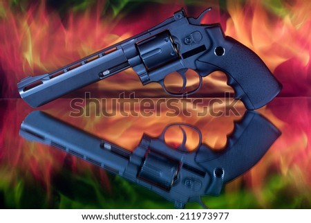 revolver on the mirror in the fire - stock photo