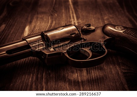 Revolver on the wooden table. Image vignetting and the yellow-orange toning - stock photo