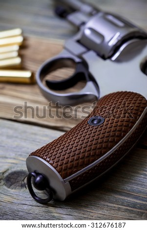 revolver pistol with ammunition on an old wooden surface. handle closeup - stock photo