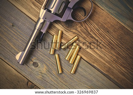 Revolver pistol with ammunition on an old wooden surface. instagram image filter retro style - stock photo