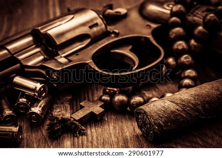 Revolver with cartridges and a rosary with cuban cigar on the wooden table. Focus on the cuban cigar. Close up view, image vignetting and the yellow-orange toning - stock photo