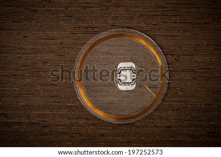 RFID Chip on dark Wenge wood Texture with Vignette - stock photo