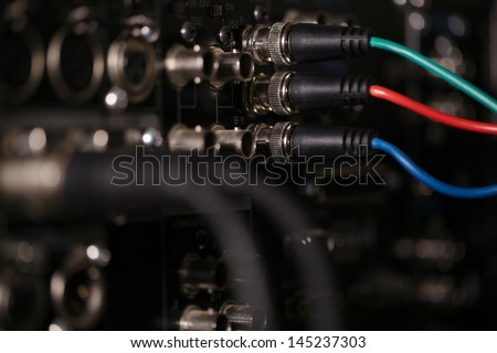 RGB video cables in the rear panel of the professional VCR. XLR audio cables in blur. - stock photo