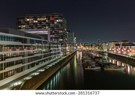 Rhine harbor in cologne with crane houses at night - stock photo