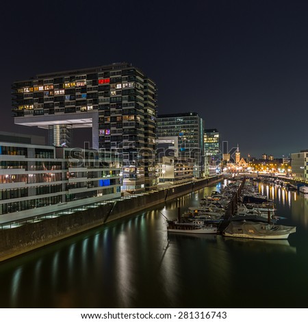 Rhine harbor with crane houses in cologne at night - stock photo