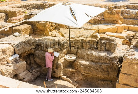 RHODES, GREECE - JUNE 28, 2014: Female archaeologist on the dig in old town Rhodes, June 28 2014, Greece.. Old Town of Rhodes is a veritable museum of the Middle Ages in the open air - stock photo
