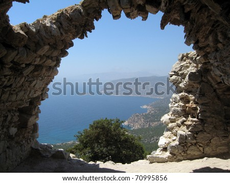 Rhodes island coast through wall opening of Monolithos castle ruins. Greece. - stock photo