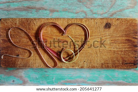 Rhubarb strings arranged in heart form at wooden cutting board - stock photo