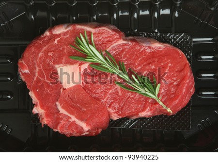 Rib-eye beef steak in plastic packing tray - stock photo