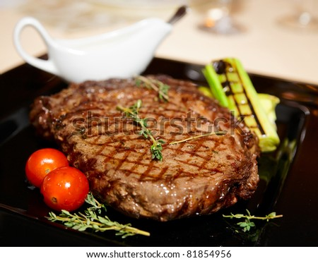 Rib eye steak served on black plate - stock photo
