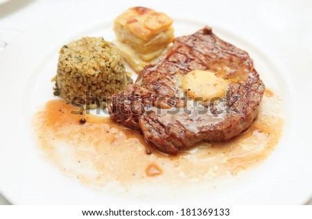 Rib eye steak with bulgur, butter and potato gratin on plate - stock photo