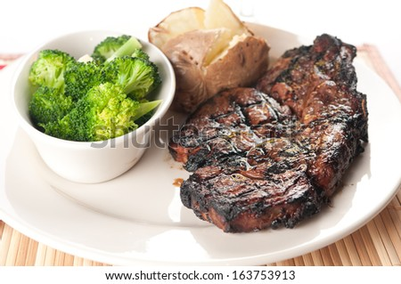 rib steak grilled to perfection with mushrooms, broccoli and baked potato - stock photo