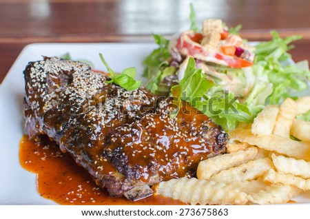 rib steak with vegetables on white plate. - stock photo