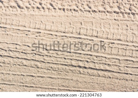 Ribbed tyre traces on dry sand. Background for articles about traveling, transport and ecology - stock photo