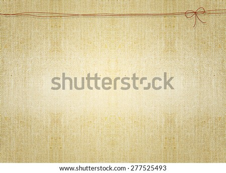 ribbon string knot over brown grungy canvas parchment background. Backdrop, invitation card design idea template wallpaper. Decoration, ornament, layout, artistic design. - stock photo