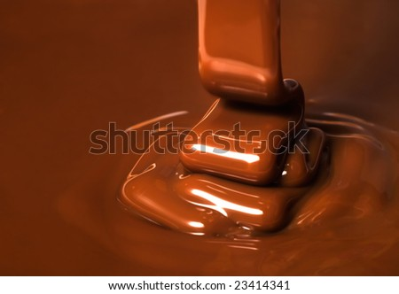 Ribbons of chocolate being poured - stock photo