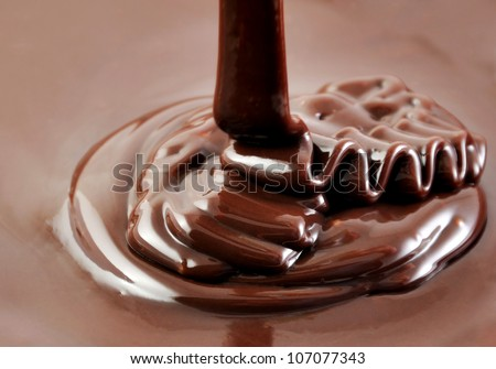 Ribbons of pouring hot chocolate, sweet cooking background - stock photo