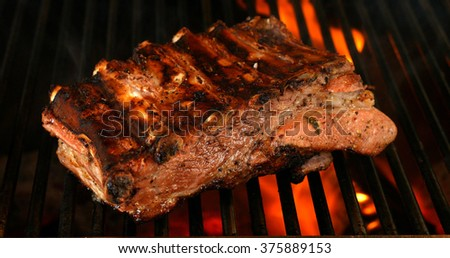 Ribs on the grill with flames - stock photo