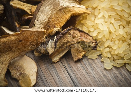 Rice and dried porcini mushrooms on table  - stock photo