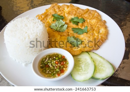 rice and omelet serve with chili in fish sauce and slice cucumber it's popular traditional Thai style food - stock photo