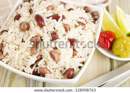 Rice and Peas - Caribbean coconut rice with red kidney beans, cowpeas and pigeon peas. Scotch bonnet chilies and lime on side. Close up. - stock photo
