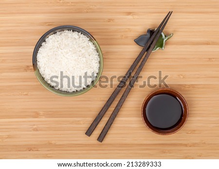Rice bowl, chopsticks and soy sauce over bamboo table - stock photo